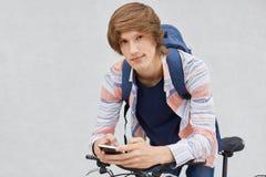 Écolier à la mode tenant la chemise de port de sac à dos utilisant le téléphone portable surfant les réseaux sociaux communiquant Photos libres de droits
