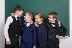 Écolier élémentaire dupant autour près du fond vide de tableau, habillé dans le costume noir classique, élève de groupe, conce d' Photos libres de droits