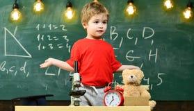Écolier élémentaire mignon avec le microscope à son bureau à la maison Jeune scientifique faisant des expériences dans sa maison photographie stock