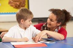 Écolier étudiant dans la salle de classe avec le professeur Image stock