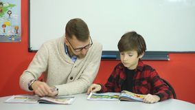 Écolier étudiant dans la salle de classe avec le professeur banque de vidéos