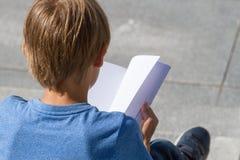 Écolier étudiant, livre de lecture dehors images libres de droits
