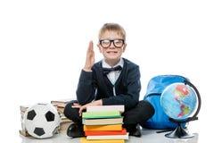 Écolier 8 années avec une main augmentée pour la réponse du l Photo stock
