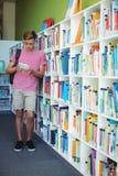 Écolier attentif à l'aide du comprimé numérique dans la bibliothèque Photos libres de droits
