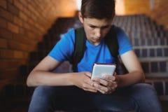 Écolier attentif à l'aide du téléphone portable sur l'escalier Photo libre de droits