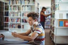 Écolier attentif à l'aide du téléphone portable tout en étudiant dans la bibliothèque Photographie stock libre de droits