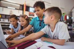 Écolier attentif utilisant l'ordinateur portable dans la bibliothèque Image stock