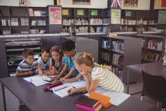 Écolier attentif utilisant le comprimé numérique dans la bibliothèque Image libre de droits