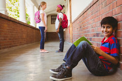 Écolier avec des amis à l'arrière-plan au couloir d'école Photographie stock libre de droits