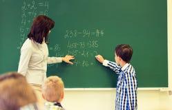 Écolier avec l'écriture de professeur de maths sur le panneau de craie images stock