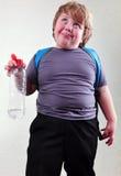 Écolier avec une bouteille de l'eau faisant des visages Photo libre de droits