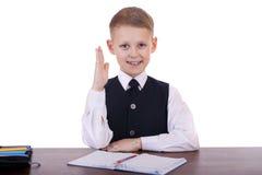 Écolier caucasien à son bureau sur le fond blanc avec la copie s Photos stock