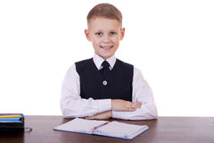 Écolier caucasien à son bureau sur le fond blanc avec la copie s Photographie stock