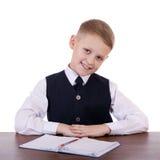 Écolier caucasien à son bureau sur le fond blanc avec la copie s Photo stock
