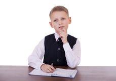 Écolier caucasien à son bureau sur le fond blanc avec la copie s Photo libre de droits