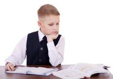 Écolier caucasien à son bureau sur le fond blanc avec la copie s Photos libres de droits