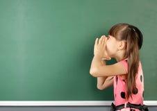 Écolier criant près du tableau noir vide d'école, l'espace de copie Image libre de droits