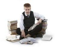 Écolier d'adolescent avec la pile des manuels Photos stock