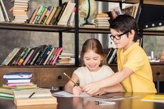 Écolier dans des lunettes aidant le camarade de classe en faisant le travail Image stock