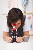 Écolier dans la classe de la science avec le microscope Image stock