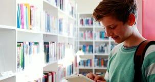 Écolier de sourire à l'aide du comprimé numérique dans la bibliothèque banque de vidéos