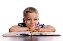Écolier de sourire avec le livre Photo stock