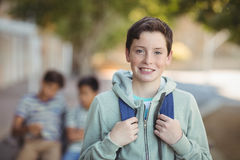 Écolier de sourire se tenant avec le cartable dans le campus Photo libre de droits
