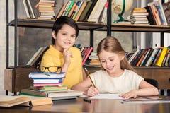 Écolier et écolière étudiant dans la bibliothèque ensemble Images libres de droits