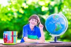 Écolier faisant des devoirs dans la cour d'école Photos stock
