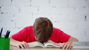 Écolier fatigué de lire le manuel banque de vidéos
