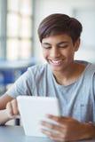 Écolier heureux à l'aide du comprimé numérique dans la salle de classe Images libres de droits