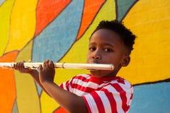 Écolier jouant l'instrument de cannelure dans le terrain de jeu d'école photo stock