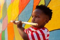Écolier jouant l'instrument de cannelure dans le terrain de jeu d'école photos stock