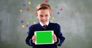 Écolier montrant le comprimé numérique dans la salle de classe clips vidéos