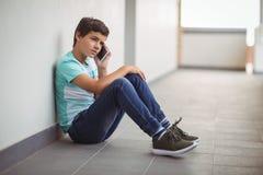 Écolier parlant au téléphone portable dans le couloir Photo stock