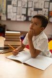 Écolier réfléchi étudiant au bureau dans une salle de classe photo stock