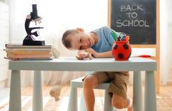 Écolier reposant à la maison le bureau menteur de salle de classe rempli de paresseux de sommeil d'écolier d'équipement pour la f photos libres de droits