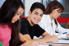 Écolier s'asseyant avec les amis féminins au bureau Images libres de droits