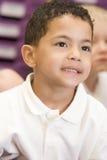 Écolier s'asseyant dans la classe primaire Photos stock