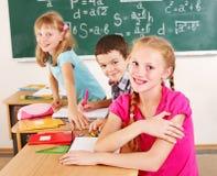 Écolier s'asseyant dans la salle de classe. Photo stock