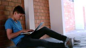 Écolier s'asseyant dans le couloir et à l'aide de l'ordinateur portable banque de vidéos