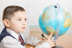 Écolier se dirigeant au globe Images libres de droits