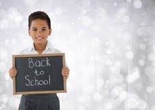Écolier se tenant de nouveau au tableau noir d'école devant le fond lumineux de bokeh photographie stock libre de droits