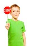Écolier tenant la petite icône rouge de signe d'arrêt Photo stock