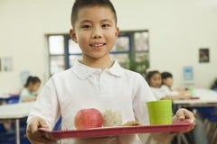 Écolier tenant le plateau de nourriture dans la cafétéria de l'école Photographie stock libre de droits