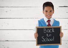 Écolier tenant le tableau noir avec de nouveau au texte d'école Image stock