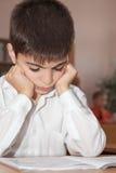 Écolier triste affichant un livre Photographie stock libre de droits