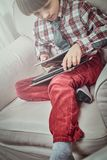 Écolier utilisant une chemise à carreaux se reposant sur un divan avec l'ensemble de comprimés à la maison photos libres de droits