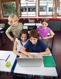 Écoliers à l'aide de l'ordinateur portable au bureau dans la salle de classe Image stock