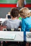 Écoliers à l'aide de la Tablette de Digital au bureau Photos libres de droits